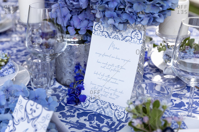 High angle of elegant sheet of paper with menu placed near decorations and tableware on banquet table during holiday celebration