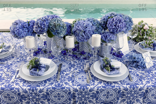 High angle of bouquets of blue flowers and candles placed near dishware on banquet table near pool in garden