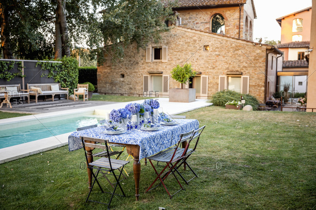 Small table with ornamental tablecloth and bouquets located on lawn near pool during wedding anniversary celebration in yard in Florence, Italy