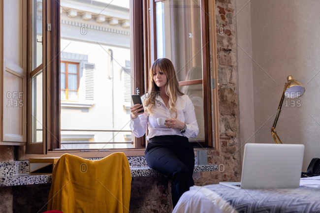 Calm female freelancer sitting with fresh coffee on windowsill in luxury hotel room and reading messages on cellphone during remote work