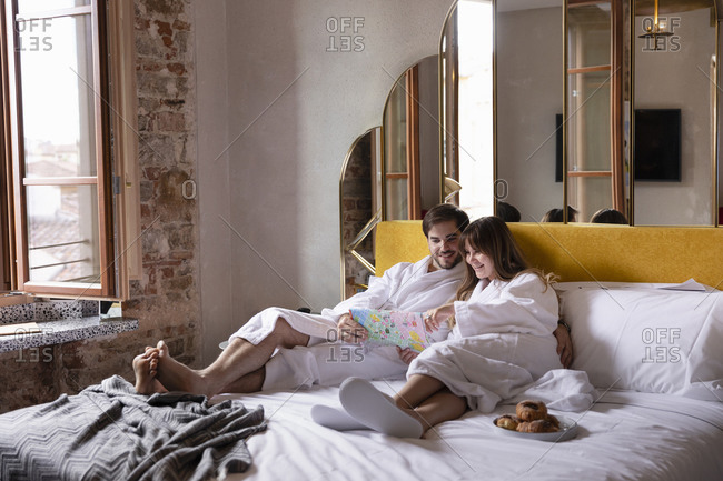 Cheerful young couple in bathrobes sitting on bed and reading tourist map while having breakfast in cozy hotel room during romantic journey in Florence in Italy