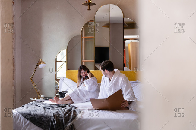 Happy young romantic couple in bathrobes reading room service menu and making order by phone during morning in stylish hotel room in Italy