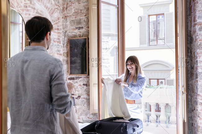 Happy young man and woman in similar outfits unpacking suitcases and choosing clothes for going out in stylish hotel room with opened balcony during summer holidays in Italy