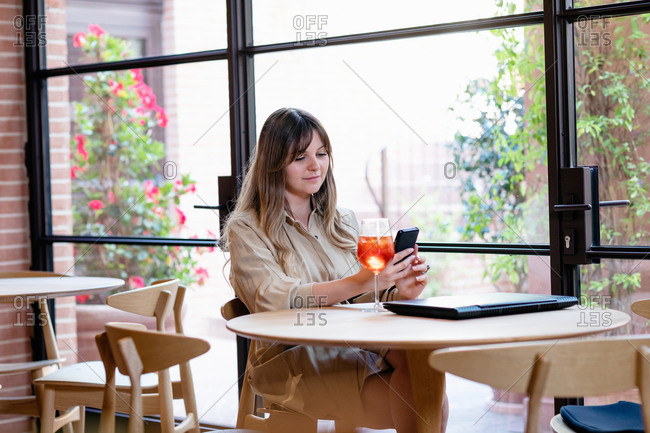 Young female blogger sitting at cafe table with glass of cocktail and laptop and browsing mobile phone while preparing content for new post during travel in Italy