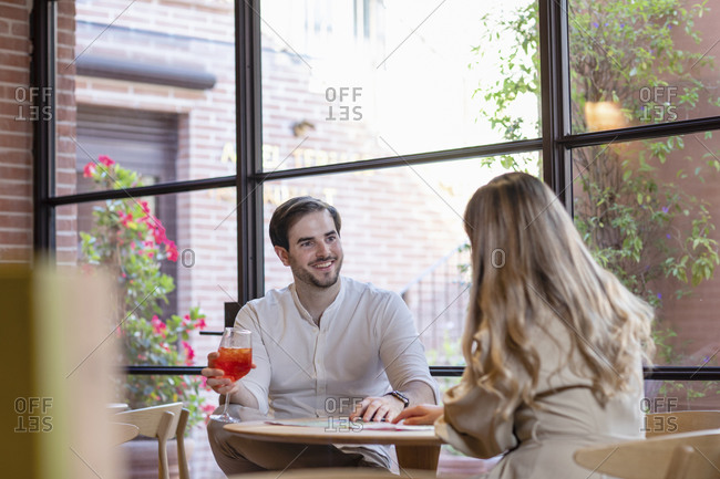 Cheerful man with cocktail smiling and looking at girlfriend while sitting at table during romantic date in cozy cafe