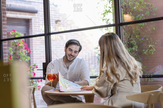 Cheerful man showing map to girlfriend while sitting at cafe table during tourist trip on weekend day