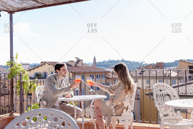 Side view of cheerful man and woman proposing toast while sitting at table on terrace of cafe during romantic date in Florence, Italy