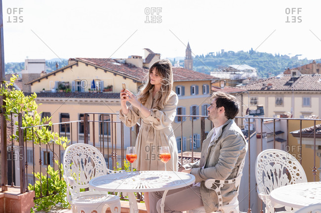 Young woman using smartphone to take picture during romantic date with boyfriend on restaurant terrace in Florence, Italy