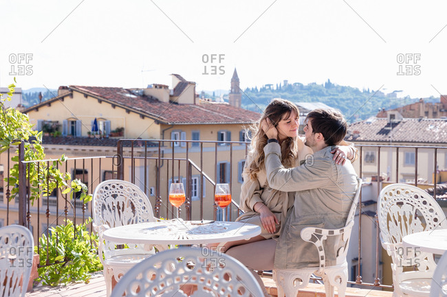 Young man embracing and touching girlfriend gently while resting on terrace of restaurant during romantic date in Florence, Italy