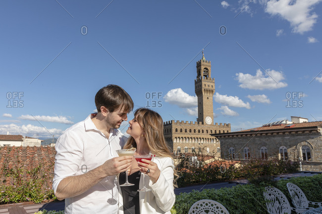 Glad young man and woman with cocktails hugging and looking at each other during romantic date in garden near Palazzo Vecchio in Florence, Italy