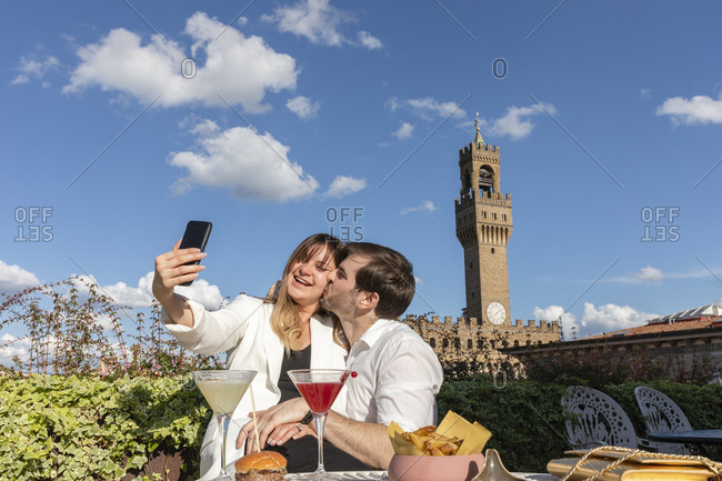 Happy man kissing and hugging smiling woman while taking selfie during romantic date in garden against famous Palazzo Vecchio in Florence, Italy
