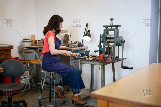Side view of craftswoman using hammer to make jewelry while sitting at workbench and working in cozy workshop