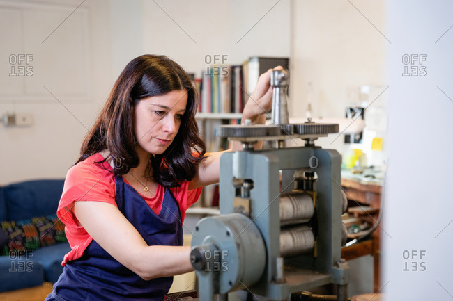 Focused craftswoman in apron using press to make jewelry while working in cozy workshop