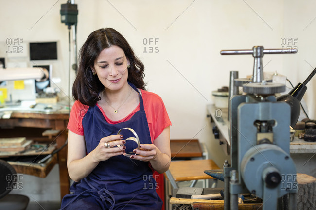 Positive female jeweler inspecting silver coil while sitting near workbench with tools and working in workshop