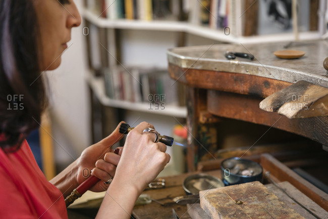 Crop craftswoman preparing gas burner for work while sitting at shabby workbench in professional studio