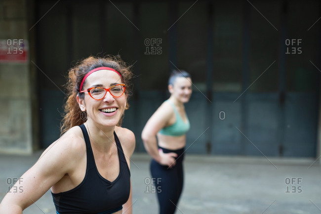 Positive female athlete in glasses and sports bra smiling and looking at camera while resting during fitness training with friend on street of Florence, Italy