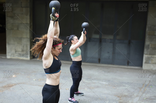 Side view of muscular female athlete lifting heavy kettlebell over head during intense workout with friend on street of Florence, Italy