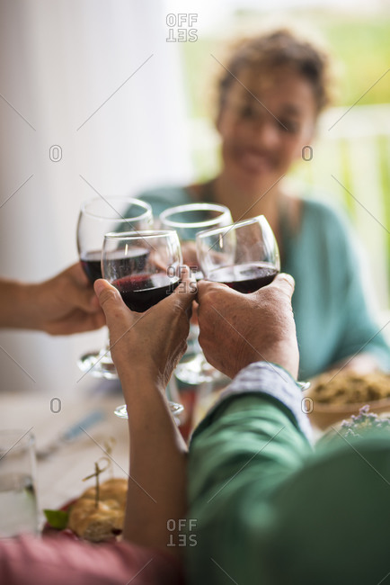 Adults toasting with red wine and glasses during a family lunch at home