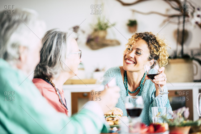 Family having lunch at home with adult woman and senior parents