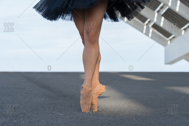 Unrecognizable female dancer dressed in black tutu on tiptoe
