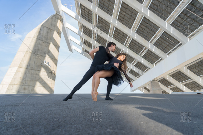 Dancers dressed in black dancing in the city under solar panels