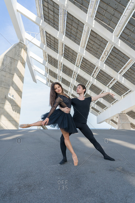 A young couple in love passionately dances on a city street under solar panels