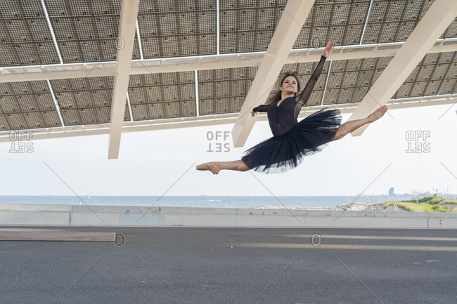 Young ballerina with black tutu jumping in the air outdoors, under big solar panel
