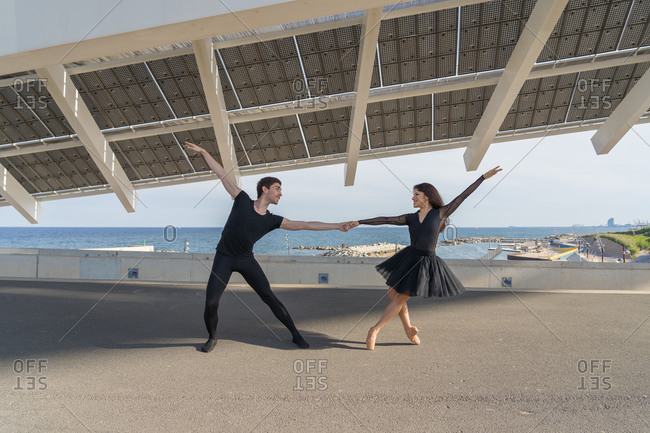 Beautiful young couple practicing dance moves off the coast in Barcelona, under solar panels