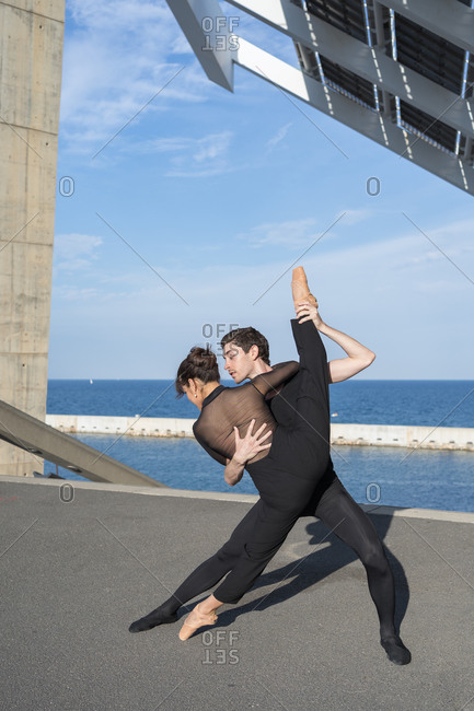 A young couple in love passionately dances on a city street near the sea