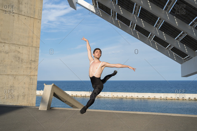 Professional man ballet dancer jumping under solar panels in the city