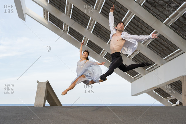 Two young dancers caught mid-air jumping in unison