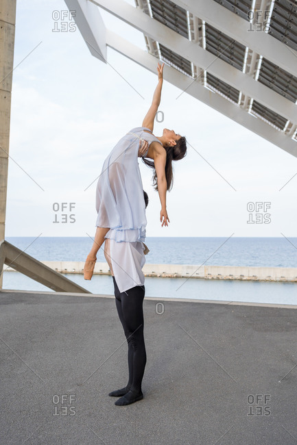 Couple performing ballet positions outdoors near the sea