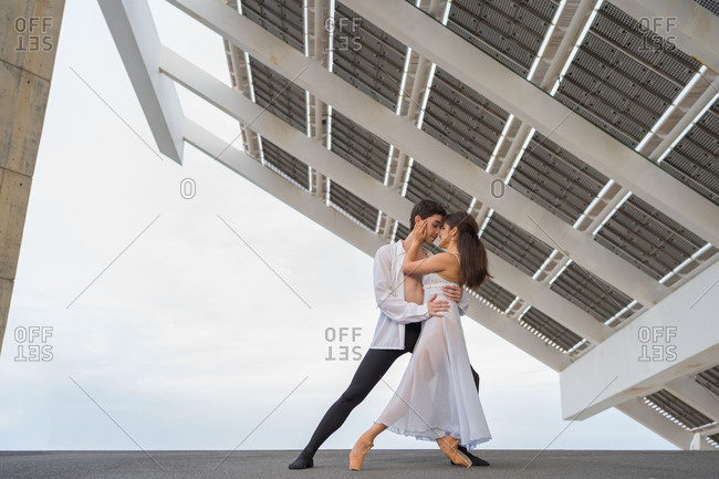 Young passionate dancers dancing outdoors under solar panels