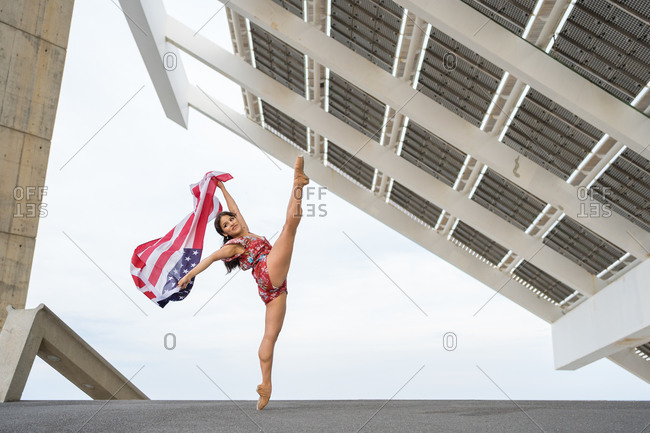 Young ballerina dancing while holding USA national flag outdoors