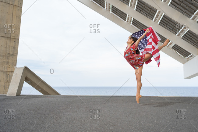 Young female woman dancing while holding USA national flag outdoors