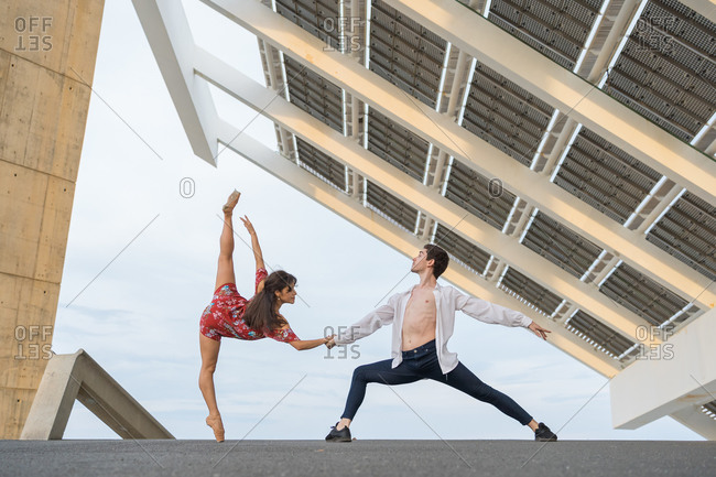 Young couple of modern ballet dancers dancing in street under solar panels