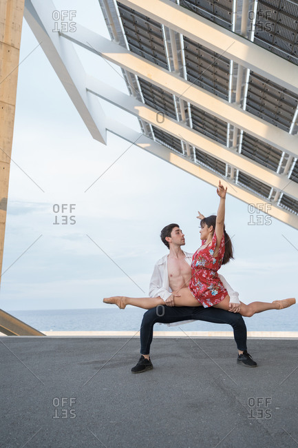 Young couple dancing in the city under solar panels