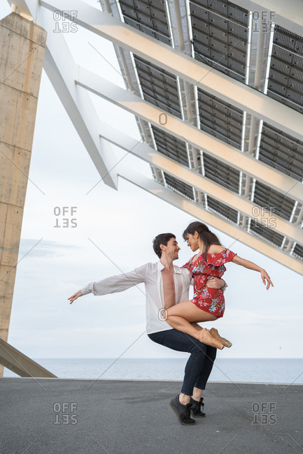 Beautiful young couple of modern ballet dancers dancing in street under solar panels