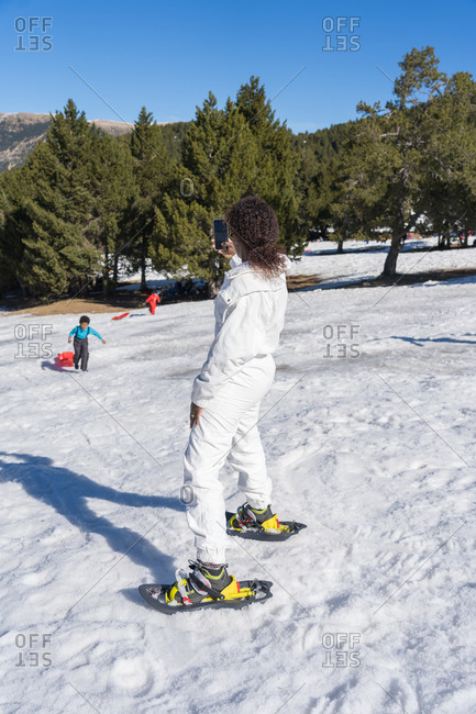 Black woman in a white jumpsuit takes a picture of her son in the snow