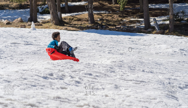 Happy black boy sledding down from the snow slope