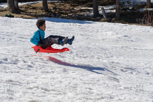 Black boy slides down from the snow slope. Enjoying the winter sledding time.