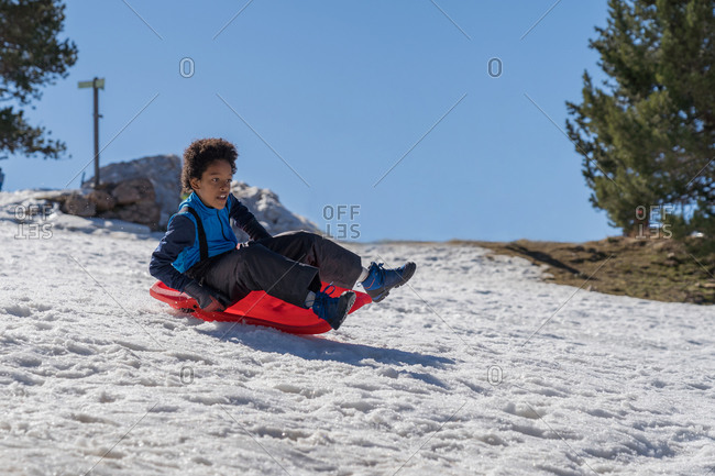 Black boy slide down from snow slope sitting in one slide.Winter activities concept image.
