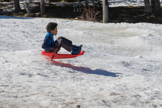 Black boy jumps on his sled down the snowy slope