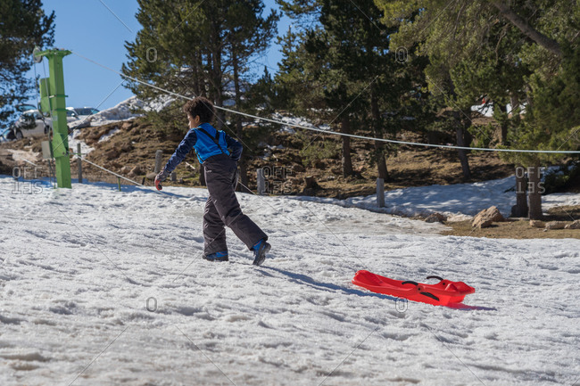 Black boy pulls the sled up the snowy mountain