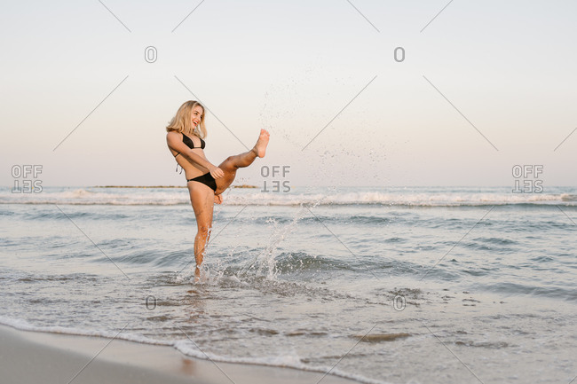 Portrait of smiling young woman in black bikini kicking the water on the beach