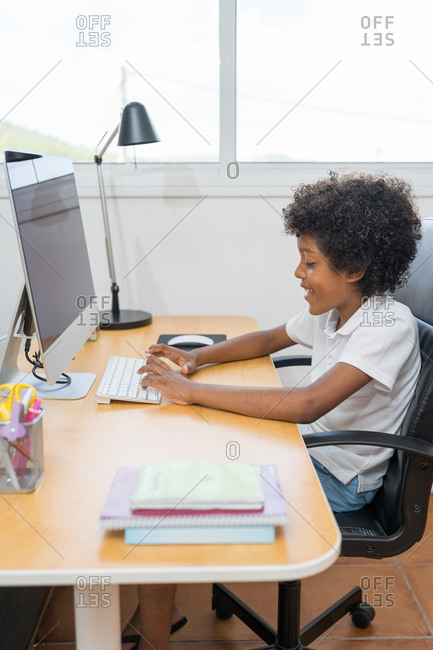 Afro american boy with curly hair spending time with computer and modern technology