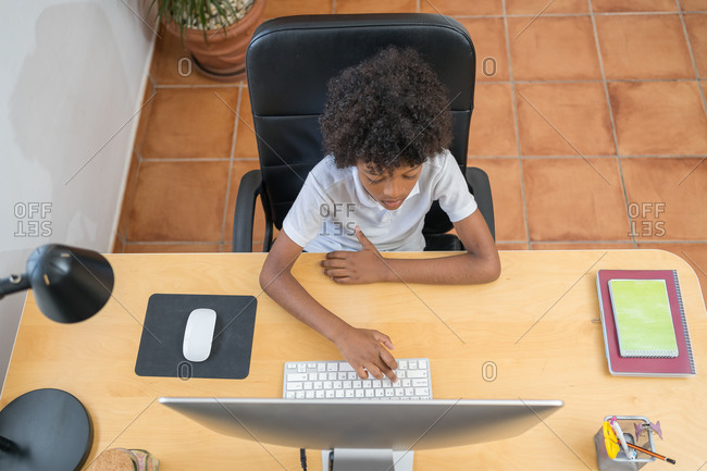 Afro american boy typing on a computer. Top view