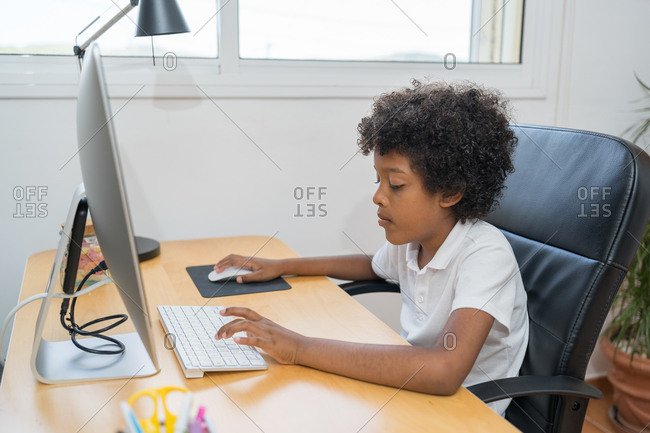 Afro american boy with white t-shirt in the computer making homework