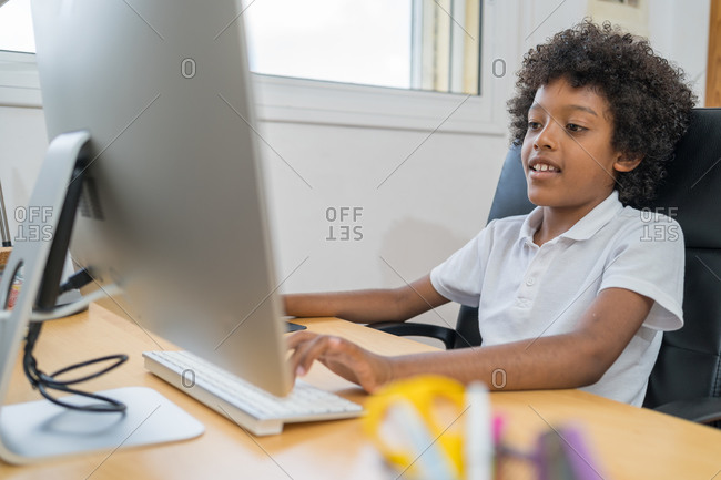 Afro american boy doing homework on computer in the living room