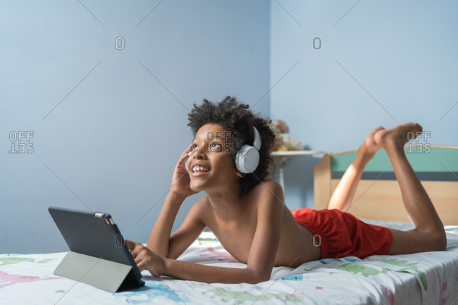 Little african american boy in headphones listening to music in the bedroom